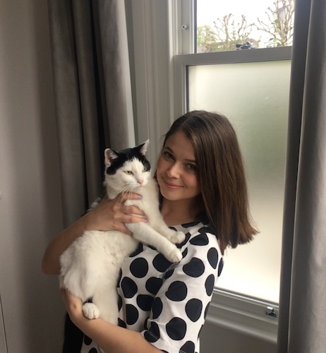 Ana holding her black and white cat while wearing a black and white shirt.