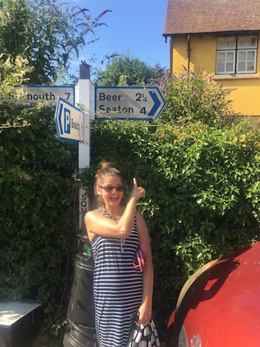 Ana pointing at a road sign that shows a place called Beer two miles away.